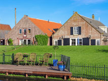 Farm houses in the Netherlands. Farm houses with lawn at dike in the Netherlands Royalty Free Stock Photos