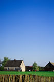 Farm houses in Poland. A simple and minimalistic composition of a single rural homestead of two houses in green field seen through a wicker fence. Clear blue sky Royalty Free Stock Image