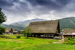 Farm houses in Shirakawa Go, Japan. Exterior of traditional gassho zukuri farm houses in field of Shirakawa Go, Japan under cloudy skies Royalty Free Stock Photography