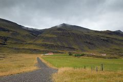 Farm in Iceland. A road leads to a farm house in Iceland, with mountains as the background Royalty Free Stock Photography