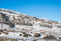 Farm on the Icelandic countryside under the mountain. On a snowy winter day royalty free stock photography