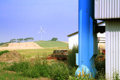 Farm industry. A picture taken on a farm, with an incinerator in the foreground and a large wind turbine in the background Royalty Free Stock Photography