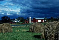 Farm land. Hay bails sit in a field with a barn in the distance. A storm brews in the distance as well Royalty Free Stock Photo