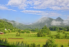 Farm Land in a Valley. Beautiful summer day in a mountain valley showing pasture land with the hay cut and bailed royalty free stock image