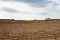 Farm landscape with plowed field. Spring landscape with arable land and rainy sky Stock Image