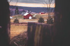 Farm Landscape Winter Pennsylvania. Pennsylvania farm filtered style. Red barn and silo and farm houses are visible. Framed by wooden fence. Winter Royalty Free Stock Photos