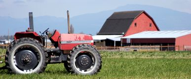 Farm Life. A serene setting on a farm with a tractor and barn royalty free stock image