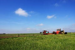 Farm Machinery in Field. Tractor and fertilizer in green field in spring in the midwest Royalty Free Stock Image