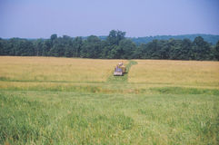 Farm machinery mowing in field Royalty Free Stock Photo
