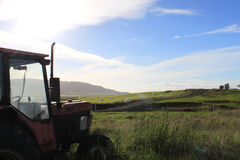 Farm meadows with tractor, grass and blue skies stock image