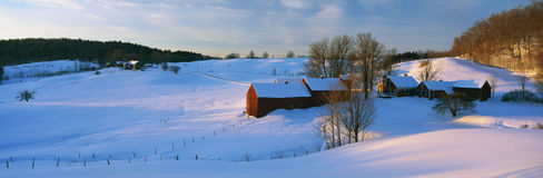 Farm in New England covered in snow. This is the Jenne Farm in Vermont at sunrise. The surrounding countryside is buried in snow. It is representative of New Stock Photography