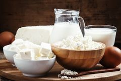 Farm organic dairy products: milk, yogurt, cream, cottage cheese. Butter, cottage cheese on a wooden background in rustic style, selective focus stock photo