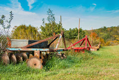 Farm Plows Waiting For Work. Vintage farm equipment sits idle waiting for time to plow the fields.  It's a beautiful fall day in West Virginia Stock Image