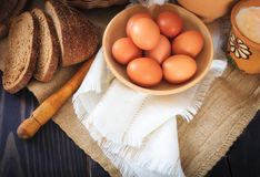 Farm products: eggs, milk, bread on a wooden table. Royalty Free Stock Image