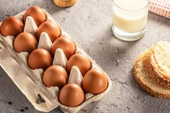 Farm raw fresh egg in pack bread milk on gray table scrambled eggs omelet fried egg Stock Photo
