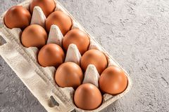Farm raw fresh egg in pack on gray table scrambled eggs omelet fried egg Stock Image