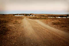 Farm road. Dirt track road on a farm in the Karoo, Eastern Cape, South Africa, showing buildings in the background Stock Photography