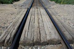 A farm road over a train track Stock Image
