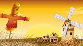 A farm with a scarecrow and a windmill Stock Image