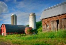 Farm Scene. Run Down Barn with Silos in the Background stock photo