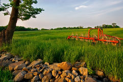 Farm Scene. Late hour view of farm equipment on grassy hill with rock wall Stock Photos