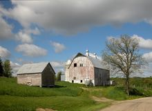 Farm Scene. Photograph of some rustic old barns on a hill in a brilliantly green country side with sunshine and clouds Stock Images