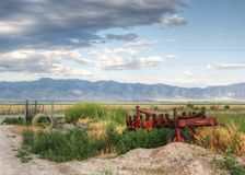Farm Scene. Farm equipment and blue mountains in hdr Royalty Free Stock Image