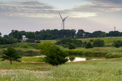 Farm scene with pond, wind farm and pastures. A Farm scene with pond, wind farm and pastures Stock Image