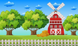 Farm scene with windmill in the field Royalty Free Stock Photo