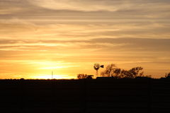 Farm Setting. Sun setting on a ranch in Fort Worth Texas. Oh, how I love Windmills Royalty Free Stock Images
