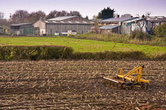 Farm sheds and machine. Working farm out buildings and arable field with cultivator Royalty Free Stock Photography
