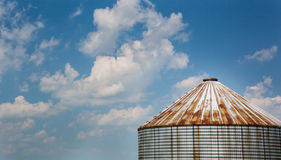 Farm silo and sky. Rusty and weathered farming silo isolated with fluffy clouds and blue sky stock photography