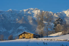 Farm in the snow and the white mountains Royalty Free Stock Images