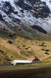Farm and snowy mountainside Royalty Free Stock Photos