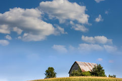 Farm in Summer. A barn sits on a hill set against a blue summer sky Royalty Free Stock Photo