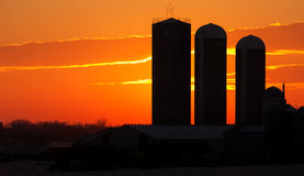 Farm Sunset. The sun setting behind a farm Stock Photos
