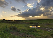 Farm Sunset with grey clouds and sun rays landscap Stock Image