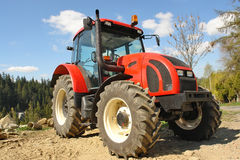Farm tractor. Modern red farm tractor parked stock photography