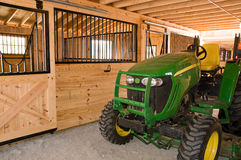 Farm tractor in barn. A view of a modern farm tractor stored inside a new wooden barn Royalty Free Stock Photography
