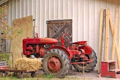 Farm tractor beside barn. Red vintage farm tractor beside wall of  barn with straw bale on trolley, steps, planks of wood and old door Royalty Free Stock Images