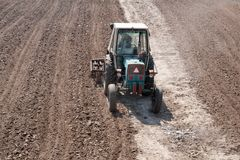 Farm tractor cultivating a plot Royalty Free Stock Photo