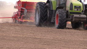 Farm tractor with device makes furrow in field stock video footage