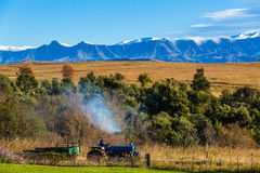 Farm Tractor Mountain Landscape. Farm tractor driver  drives out for the days  work first snowfall for the season Stock Photography