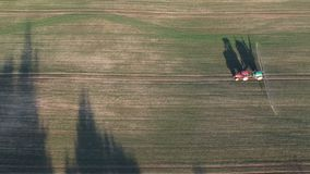 Farm tractor in evening spraying autumn time crop field with sprouts, aerial stock footage