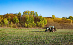 Farm tractor on the field in Europe. In the fall Royalty Free Stock Image