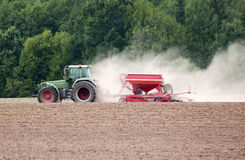 Farm tractor on field. Green farm tractor on field with forest in the background stock photography