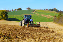 Farm tractor on the field working Stock Photo