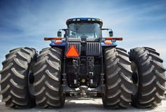 Farm tractor on huge wheels stock image