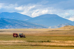 Farm tractor in mountain valley. Old farming tractor equipment sitting in agriculture field in a mountain valley of colorado - agricultural farming industry Royalty Free Stock Photos