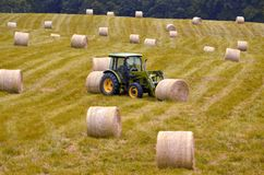 Farm tractor moving hay bales  Stock Images